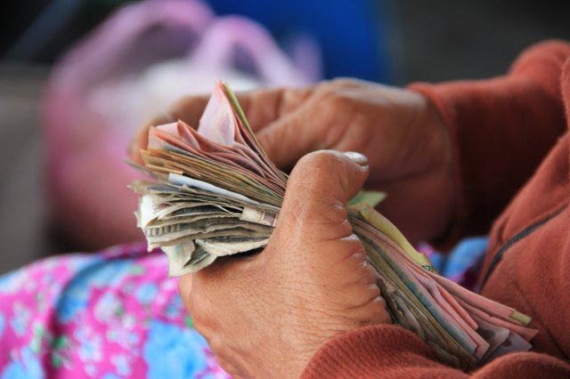 Closeup of hands holding paper money