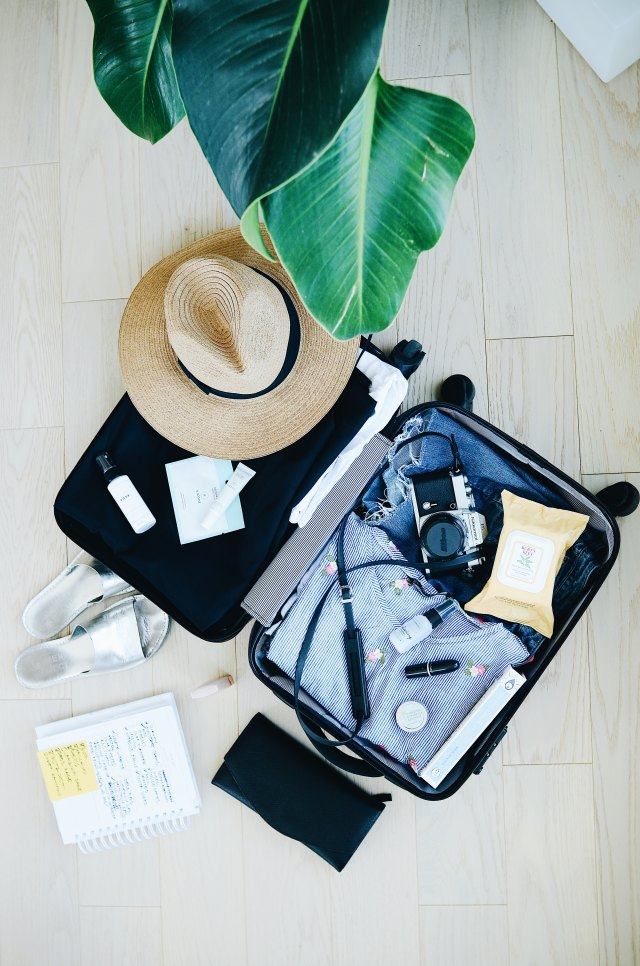Open suitcase with clothes, hat, camera